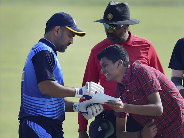 Must-see pic: MS Dhoni signs autograph for a crazy fan while batting