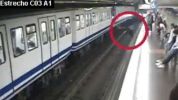 A Woman distracted by mobile phone falls in front of oncoming train