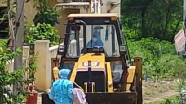 A woman dead body taken to burial ground by jcb in nizamabad district.