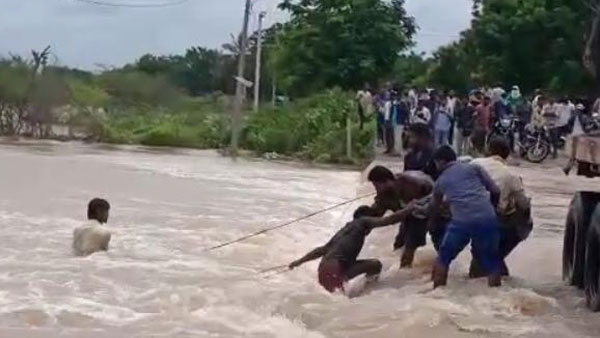 two youth on bike trying to cross culvert washed way in floods but saved by locals